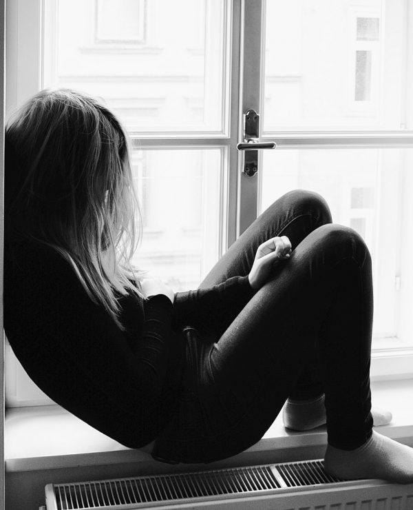 Tinejdžer pod stresom, tinejdžerka, duga kosa, tužna, usamljena, sedi na prozoru